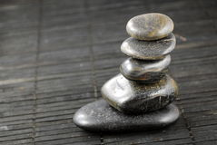 Black zen stones on bamboo. Place mat, concept of balance Royalty Free Stock Photos