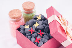 Black zen stones in a red gift box with red and yellow ixora flowers Stock Photos