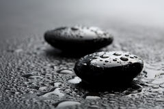 Black zen stones with water drops. Black shiny zen stones with water drops over black background Royalty Free Stock Image