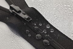Black zipper. A black zipper opened to a gray surface sprayed with water droplets Royalty Free Stock Photos