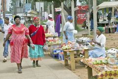 Black Zulu women in brightly colored red dresses walk past produce vendors in Zulu village in Zululand, South Africa Royalty Free Stock Image
