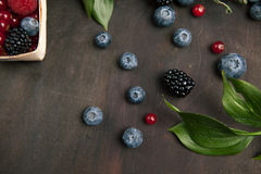 Blackberries and bilberries with leaves on the wooden table. Top view. Blackberries and bilberries with leaves on the wooden table, close up. Concept for healthy Stock Photo