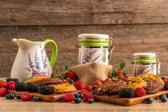 Blackberries, blueberries, raspberries, cookies and white ceramic vessels royalty free stock photos