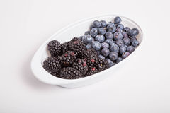 Blackberries and Blueberries in White Dish on White Background Royalty Free Stock Photos