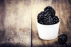 Blackberries in a bowl on brown wooden table Stock Image