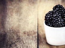 Blackberries in a bowl on brown wooden table Royalty Free Stock Photo