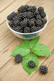 Blackberries in bowl and leaves on table Stock Photography
