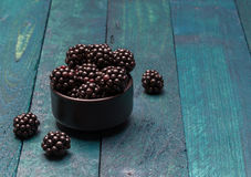 Blackberries in a bowl on petrol colored wooden background Royalty Free Stock Photography