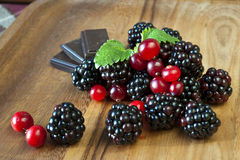 Blackberries and cranberries with chocolate on woo. Blackberries and cranberries with chocolate and mint on wooden dish/plate. Closeup Stock Images