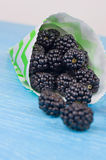 Blackberries in cup on a wooden table. Macro image.selective focus Stock Image