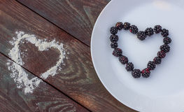 Blackberries in the form of heart on a white plate on a wooden background. Stock Photo