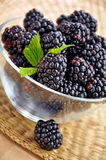 Blackberries in a glass bowl. Fresh blackberries in a glass bowl on a straw mat Royalty Free Stock Images