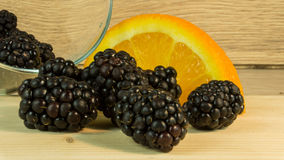 Blackberries in a glass and oranges Royalty Free Stock Images