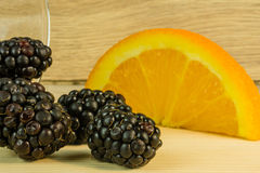 Blackberries in a glass and oranges Stock Images