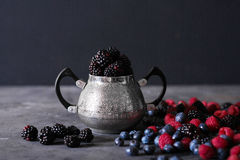 Blackberries in iron decorative vase on a dark abstract background. Stock Photo