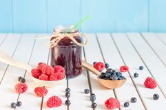Blackberries jam in mason jar and fresh raspberry. Blueberry on a wooden table. Macro image, selective focus Royalty Free Stock Photo