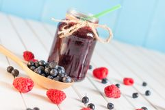 Blackberries jam in mason jar and fresh raspberry. Blueberry on a wooden table. Macro image, unique perspective, selective focus Royalty Free Stock Image