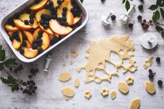 Blackberries and Peach Cobbler or Fruit Pie Preparation. On white background stock photography