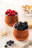 Blackberries and raspberries in ceramic pots. Close-up of blackberries and raspberries on table in kitchen. Scattered bilberries Royalty Free Stock Photography