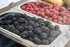 Blackberries and raspberries on display counter in metal utensil. Blackberries and raspberries in metal dishes on the display case Stock Images