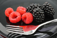 Blackberries, raspberries and a fork. On a black plate background Royalty Free Stock Photos