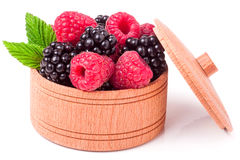 Blackberries and raspberries with leaves in a wooden bowl isolated on white background Royalty Free Stock Image