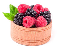 Blackberries and raspberries with leaves in a wooden bowl isolated on white background.  Royalty Free Stock Photography