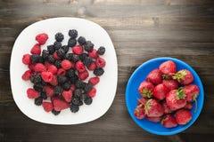 Blackberries and raspberries on a plate. blackberries and raspberries on wooden background. vegetarian food.  stock photos