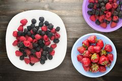 Blackberries and raspberries on a plate. blackberries and raspberries on wooden background. vegetarian food stock images
