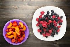Blackberries and raspberries on a plate. blackberries and raspberries on wooden background. vegetarian food.  stock image