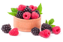 Blackberries and raspberries spilled from wooden bowl isolated on white background Stock Photo