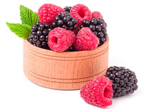 Blackberries and raspberries spilled from wooden bowl isolated on white background Royalty Free Stock Photos
