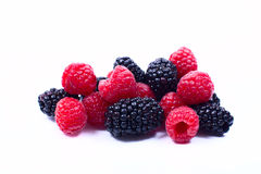 Blackberries and raspberries on a white background. Handful of juicy, tasty blackberries and raspberries on a white background closeup Royalty Free Stock Photos