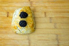 Blackberries on scone - blurred wooden table in background. Poppy seed scone topped with delicious fresh blackberries with copy space for advert Stock Images