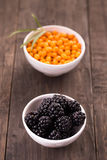 Blackberries and sea buckthorn on wooden table Stock Image