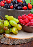 Blackberries, strawberry, raspberry and grapes in a wooden Stock Photography