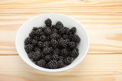 Blackberries in a white bowl on wooden table stock images