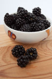 Blackberries in a white plate. On a wooden board Stock Photography