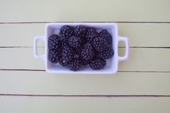 Blackberries on white tray on green wood from above stock photo