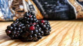 Blackberries on wooden table. Close-up of blackberries on a wooden table with a dark cloth in the background Royalty Free Stock Photos