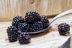 Blackberry σε ένα κουτάλι και ένα ξύλινο υπόβαθρο Στοκ Φωτογραφίες