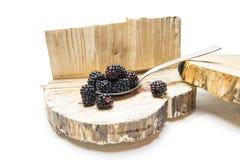Blackberry σε ένα κουτάλι και ένα ξύλινο υπόβαθρο Στοκ Φωτογραφία