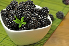 Blackberry. Blackberries in a white bowl on a green pad on a wooden table Stock Photography