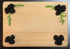 Blackberry And Arugula. Frame composition on a wooden board royalty free stock images