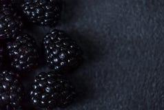 Blackberry bakgrund Closeup av nya björnbär på svart t Arkivbilder