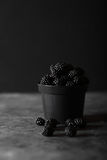 Blackberry. Blackberries in black decorative vase on a dark abstract background Stock Images