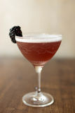 Blackberry cocktail with a wooden background. Blackberry cocktail in an elegant glass on a walnut wood table Stock Photos