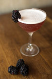 Blackberry cocktail with a wooden background. Blackberry cocktail in an elegant glass on a walnut wood table with blackberries surrounding it Stock Images