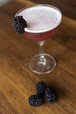 Blackberry cocktail with a wooden background. Blackberry cocktail in an elegant glass on a walnut wood table with blackberries surrounding it Stock Photo