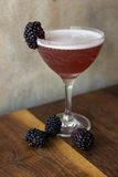 Blackberry cocktail with a wooden background. Blackberry cocktail in an elegant glass on a walnut wood table with blackberries surrounding it Stock Image